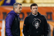 Head coaches (L-R) Chris Petersen of the Washington Huskies and Mike Gundy of the Oklahoma State Cowboys talk during warm ups to the TicketCity Cactus Bowl at Sun Devil Stadium on January 2, 2015 in Tempe, Arizona.