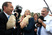 Australian Opposition Leader, Tony Abbott, his daughter Frances, and Joe Hockey, hold a puppy at Victoria Guide Dogs on September 6, 2013 in Melbourne, Australia. With just one day left in the campaign the Liberal-National Party coalition had one of their first stumbles, by releasing a policy to implement an opt-out internet filter, but then abandoning it within hours. The conservative Liberal-National Party coalition looks set to form government in tomorrow's Federal Election.