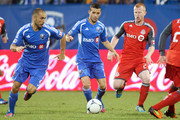Felipe Martins #7 of the Montreal Impact passes the ball to teammate Marco Di Vaio #9 at the Saputo Stadium on June 27, 2012 in Montreal, Quebec, Canada.  The Toronto FC defeated the Impact 3-0.