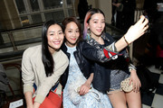 (L-R) Liu Wen, Janine Chang, and Irene Kim watch Tory Burch collection during Fall 2016 New York Fashion Week at David Geffen Hall on February 16, 2016 in New York City.