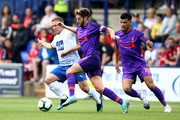 Adam Lallana of Liverpool battles with Jay Harris of Tranmere Rovers during the Pre-Season Friendly match between Tranmere Rovers and Liverpool at Prenton Park on July 11, 2018 in Birkenhead, England.