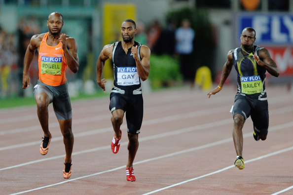 Tyson Gay of United States (C) competes ahead of Asafa Powell of Jamaica (L) ...