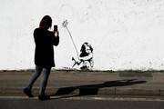 A member of the public takes a photograph on her phone of a Banksy mural that has been modified to depict the current COVID-19  pandemic on April 21, 2020 in Southampton, England. The British government has extended the lockdown restrictions first introduced on March 23 that are meant to slow the spread of COVID-19.