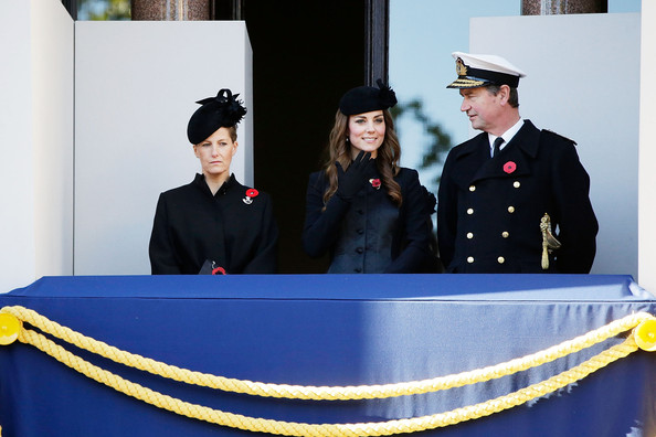 Catherine, Duchess of Cambridge smiles from a balcony, accompanied by Sophie, Countess of Wessex (L) and Vice Admiral Sir Timothy  Laurence (R) as they watch a wreath laying ceremony at the Cenotaph on Whitehall on November 10, 2013 in London, United Kingdom. People across the UK gathered to pay tribute to service personnel who have died in the two World Wars and subsequent conflicts, as part of the annual Remembrance Sunday ceremonies.