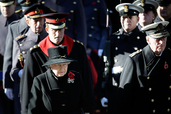 Queen Elizabeth II, followed by Prince Harry, leaves the Foreign and Commonwealth Office shortly before 11am to take part in a wreath laying ceremony at the Cenotaph  on Whitehall on November 10, 2013 in London, England. People across the UK gathered to pay tribute to service personnel who have died in the two World Wars and subsequent conflicts, as part of the annual Remembrance Sunday ceremonies.