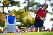 Lexi Thompson of the United States hits a tee shot while So Yeon Ryu of South Korea watches on the 9th hole during the Singles match on day four of the UL International Crown at Jack Nicklaus Golf Club on October 7, 2018 in Incheon, South Korea.
