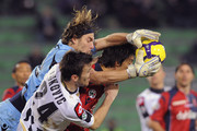 Goalkeeper Federico Marchetti of Cagliari catches the ball in the air ahead of Aleksandar Lukovic (R) of Udinese during the Serie A match between Udinese Calcio and Cagliari Calcio at Stadio Friuli on February 24, 2010 in Udine, Italy.