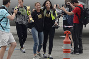 Captain Christie Rampone (C) holds the FIFA Women's World Cup trophy as she walks off the plane with goalkeeper Hope Solo (R) and forward Abby Wambach (L) after they arrived at Los Angeles International Airport July 6, 2015 in Los Angeles, California.