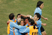 Uruguay players congratulate Diego Forlan of Uruguay on scoring his team's first goal from a free kick during the 2010 FIFA World Cup South Africa Quarter Final match between Uruguay and Ghana at the Soccer City stadium on July 2, 2010 in Johannesburg, South Africa.