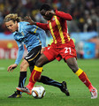 Diego Forlan of Uruguay battles with Kwadwo Asamoah of Ghana during the 2010 FIFA World Cup South Africa Quarter Final match between Uruguay and Ghana at the Soccer City stadium on July 2, 2010 in Johannesburg, South Africa.