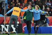 Diego Lugano (L) congratulates Diego Forlan of Uruguay as he celebrates scoring his team's first goal from a free kick during the 2010 FIFA World Cup South Africa Quarter Final match between Uruguay and Ghana at the Soccer City stadium on July 2, 2010 in Johannesburg, South Africa.
