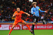 John Heitinga of the Netherlands challenges Diego Forlan of Uruguay during the 2010 FIFA World Cup South Africa Semi Final match between Uruguay and the Netherlands at Green Point Stadium on July 6, 2010 in Cape Town, South Africa.