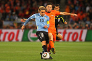 Mark Van Bommel of the Netherlands tackles Diego Forlan of Uruguay during the 2010 FIFA World Cup South Africa Semi Final match between Uruguay and the Netherlands at Green Point Stadium on July 6, 2010 in Cape Town, South Africa.