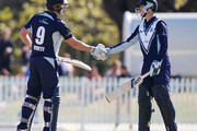 Cameron White of Victoria (L) celebrates his half century with Peter Handscomb of Victoria during the JLT One Day Cup match between Victoria and South Australia at Junction Oval on September 30, 2018 in Melbourne, Australia.