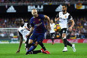 Andres Iniesta of FC Barcelona competes for the ball with Geoffrey Kondogbia (L) and Martin Montoya of Valencia CF during the La Liga match between Valencia and Barcelona at Mestalla stadium on November 26, 2017 in Valencia, Spain.