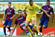 Denis Cheryshev of Villarreal is tackled by Sergio Busquets of Barcelona during the La Liga match between Villarreal CF and FC Barcelona at El Madrigal stadium on August 31, 2014 in Villarreal, Spain.