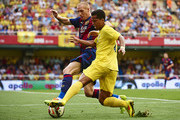Giovani Dos Santos of Villarreal is tackled by Mathieu (L) of Barcelona during the La Liga match between Villarreal CF and FC Barcelona at El Madrigal stadium on August 31, 2014 in Villarreal, Spain.