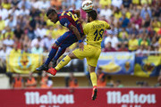 Dani Alves (L) of Barcelona competes for a high ball with Jaume Costa of Villarreal during the La Liga match between Villarreal CF and FC Barcelona at El Madrigal stadium on August 31, 2014 in Villarreal, Spain.