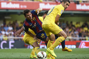 Lionel Messi of Barcelona is tackled by Cani (R) and Mateo Pablo Musacchio during the La Liga match between Villarreal CF and FC Barcelona at El Madrigal stadium on August 31, 2014 in Villarreal, Spain.