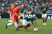 Giovani Dos Santos #10 of Mexico falls to the ground against Aaron Ramsey #10 of Wales during the second half of their friendly international soccer match at the Rose Bowl on May 28, 2018 in Pasadena, California.
