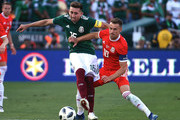 Hector Herrera #16 of Mexico is pressured by Aaron Ramsey #10 of Wales during the first half of their friendly international soccer match at the Rose Bowl on May 28, 2018 in Pasadena, California.