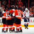 Kimmo Timonen #44 of the Philadelphia Flyers is congratulated by teammates after he scored a goal to tie the game late in the third period of an NHL hockey game as Alex Ovechkin #8 of the Washington Capitals skates with his head down at Wells Fargo Center on March 31, 2013 in Philadelphia, Pennsylvania.  Flyers won 5-4 in overtime.