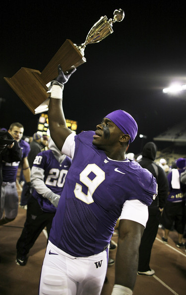 Linebacker Donald Butler #9 of the Washington Huskies holds the Apple Cup Trophy after defeating the Washington State Cougars 30-0 on November 28, 2009 at Husky Stadium in Seattle, Washington.