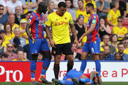 Troy Deeney of Watford confronts Mamadou Sakho of Crystal Palace after Patrick van Aanholt of Crystal Palace goes down during the Premier League match between Watford and Crystal Palace at Vicarage Road on April 21, 2018 in Watford, England.
