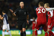 Shkodran Mustafi (C) and Jack Wilshere (R) of Arsenal protest to Referee Mike Dean during the Premier League match between West Bromwich Albion and Arsenal at The Hawthorns on December 31, 2017 in West Bromwich, England.