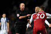 Referee Mike Dean speaks with Jack Wilshire of Arsenal during the Premier League match between West Bromwich Albion and Arsenal at The Hawthorns on December 31, 2017 in West Bromwich, England.