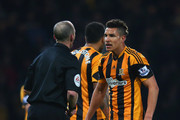 Referee Mike Dean gives Jake Livermore of Hull City a yellow card during the Barclays Premier League match between West Ham United and Hull City at Boleyn Ground on March 26, 2014 in London, England.