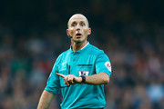 Referee Mike Dean in action during the Barclays Premier League match between West Ham United and Newcastle United at Boleyn Ground on November 29, 2014 in London, England.