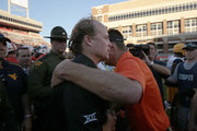 Head coach Dana Holgorsen of the West Virginia Mountaineers (L) greets head coach Mike Gundy of the Oklahoma State Cowboys after their game October 25, 2014 at Boone Pickens Stadium in Stillwater, Oklahoma. The Mountaineers defeated the Cowboys 34-10.