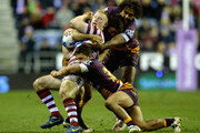 Liam Farrell of Wigan Warriors is tackled by Sam Thaiday and Kodi Nikorima of Brisbane Broncos during the World Club Series match between Wigan Warriors and Brisbane Broncos at DW Stadium on February 21, 2015 in Wigan, England.