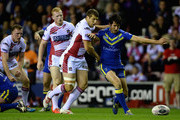 Tony Clubb of Wigan Warriors and Stefan Ratchford of Warrington Wolves battle for a loose ball during the First Utility Super League Qualifying Semi-Final match between Wigan Warriors and Warrington Wolves at DW Stadium on October 3, 2014 in Wigan, England.