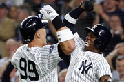 Aaron Judge #99 of the New York Yankees celebrates with Andrew McCutchen #26 after hitting a two run home run in the first inning against the Oakland Athletics during the American League Wild Card Game at Yankee Stadium on October 03, 2018 in the Bronx borough of New York City.