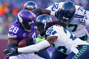 Richard Sherman #25 of the Seattle Seahawks and Michael Bennett #72 attempt to tackle Adrian Peterson #28 of the Minnesota Vikings in the first quarter during the NFC Wild Card Playoff game at TCFBank Stadium on January 10, 2016 in Minneapolis, Minnesota.