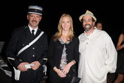 """Actress Lisa Kudrow and author William Widmaier pose for a photo with a French police officer at William Widmaier's """"A Feast At The Beach"""" book party hosted by the consul general of France on October 12, 2010 in Beverly Hills, California."""