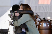 Actor Lupita Nyong'o (L) and singer Idina Menzel hug onstage during the Women's March Los Angeles 2018 on January 20, 2018 in Los Angeles, California.