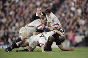 David Rees #14, Lawrence Dallaglio (L) and Phil de Glanville of England tackle Jonah Lomu of New Zealand during the match against the New Zealand All Blacks Touring side on 6 December 1997 at the Twickenham Stadium, London, England.