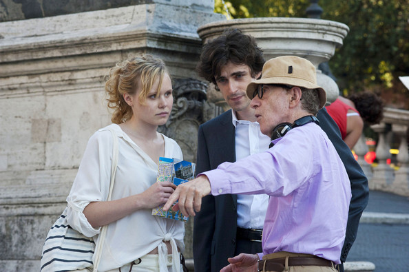 "Allison Pill (blonde hair), Flavio Parenti (white button down shirt) and Judy Davis (brown jacket) perform scenes and take direction on the set of Woody Allen's (blue shirt) latest film ""Bop Decameron"" filming in Rome. Judy davis and Flavio Perenti are also depicted on set while Woody Allen's production assistants take care of everything on the set down to the polishing of shoes."