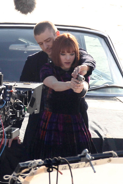 "Amanda Seyfried and Justin Timberlake film an action scene involving a prop gun for their upcoming thriller ""Now"". Amanda sported a short red wig after recently being photographed holding hands with Ryan Phillippe."