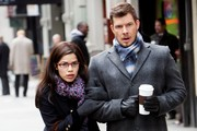 "America Ferrera films scenes for ""Ugly Betty"" with co-star Eric Mabius. Ferrera is seen filming a scene where her character falls while holding onto Mabius's arm. Marbles are also pictured on the ground as a crew member puts Ferrera's heels on for her (with her uggs close by)."