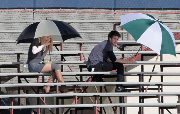 "Andrew Garfield and co-star Emma Stone seen on a break from filming ""Spiderman 4"". Andrew Garfield - the new Peter Parker/Spiderman - listened to his Ipod while Stone ate lunch. The pair were filming a kissing scene for the upcoming film in Los Angeles. Garfield, best known for his role in the recent film ""The Social Network,"" is seen sitting on bleachers with co-star Stone. Both stars stayed bundled in thick coats and gloves. Garfield has reportedly been training for his ""Spider-Man"" body, making sure to get in shape for the franchise reboot."