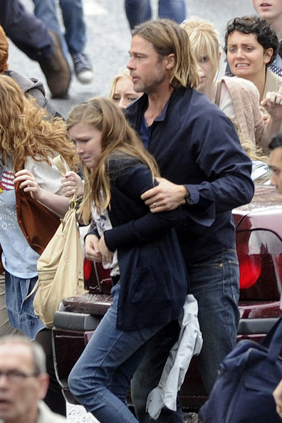 "Brad Pitt gets into role on the set of his new movie  ""World War Z"" . Glasgow's George Square was rocked with explosions , gunfire and screams as part of a scene which sees Brad getting out of his crashed Volvo and trying to get his family to safety in the confusion and crowds."