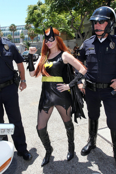 CAPED CRUSADER: Phoebe Price wears a Batwoman costume and poses on a police motorcycle during Comic-Con.