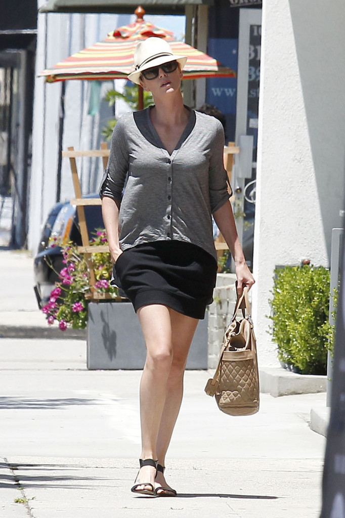 Charlize Theron, dressed in a loose grey sweater and black skirt, heads out around Los Angeles.