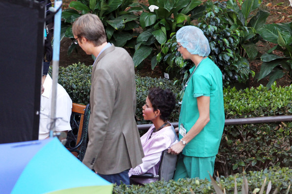 "IS THAT YOU HALLE? Halle Berry seen being wheeled around and wearing heavy facial prosthetics while filming ""Truth or Dare"" in Los Angeles in a wheelchair. The actress is later ushered in between takes, covered by a jacket, and sporting fake breast implants."