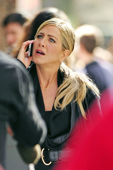 "Jennifer Aniston has an emotionally charged conversation on her iPhone during a scene for her upcoming comedic film ""Wanderlust"" in New York City. The 41 year old actress, sporting a sleek low ponytail, struts her stuff down a busy sidewalk in a cinched black sweater outfit and black leggings."