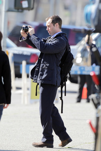 "Jude Law sulks around with a backpack during a scene for his upcoming film ""Contagion"" on a sunny day in Los Angeles. The actor, who recently split yet again from girlfriend Sienna Miller, walked around in a suit, carrying a backpack and holding onto a camera. He later was spotted speaking to a group of soldiers, with one of them taking photographs of Law."